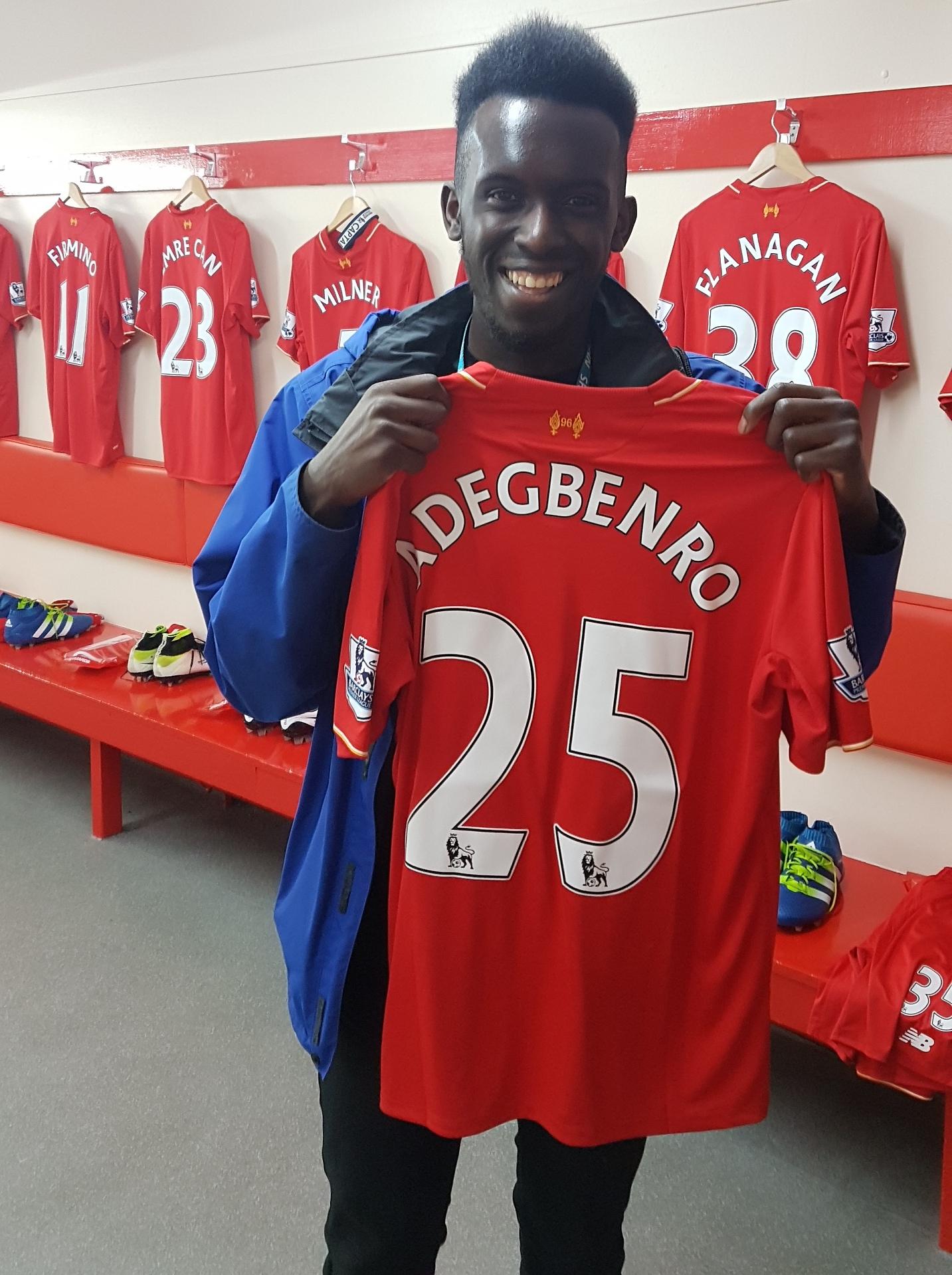 Emini holding up a Liverpool FC shirt